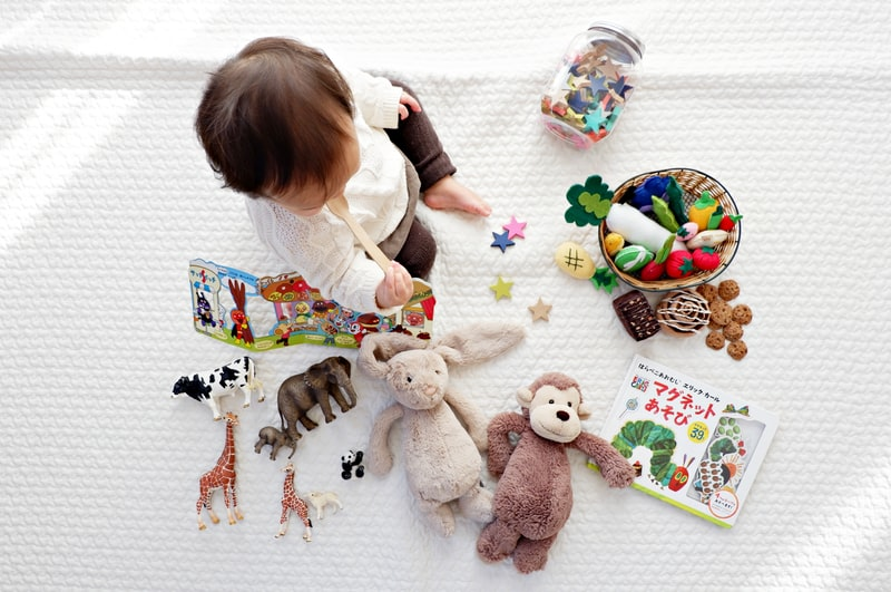A group of stuffed animals sitting next to a baby