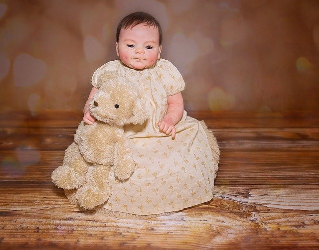 A baby holding a teddy bear sitting on top of a wooden table