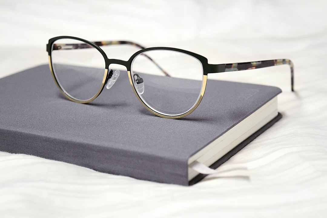 A pair of glasses on a bed