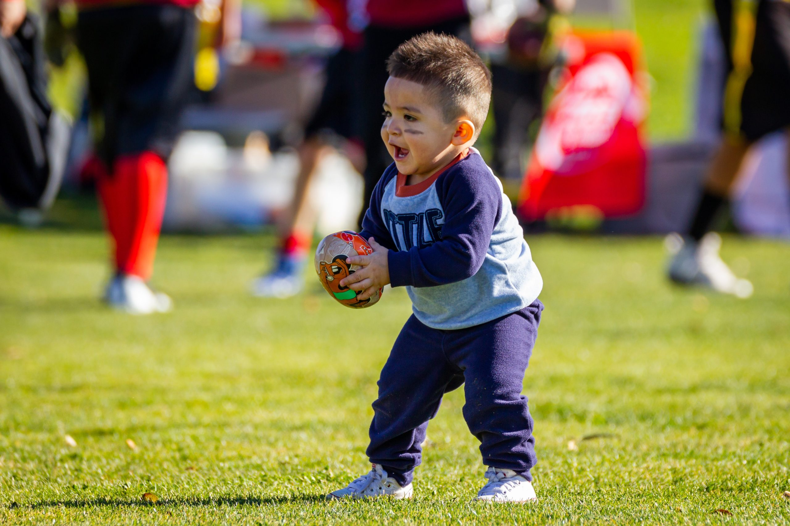 A young boy holding a football ball on a field
